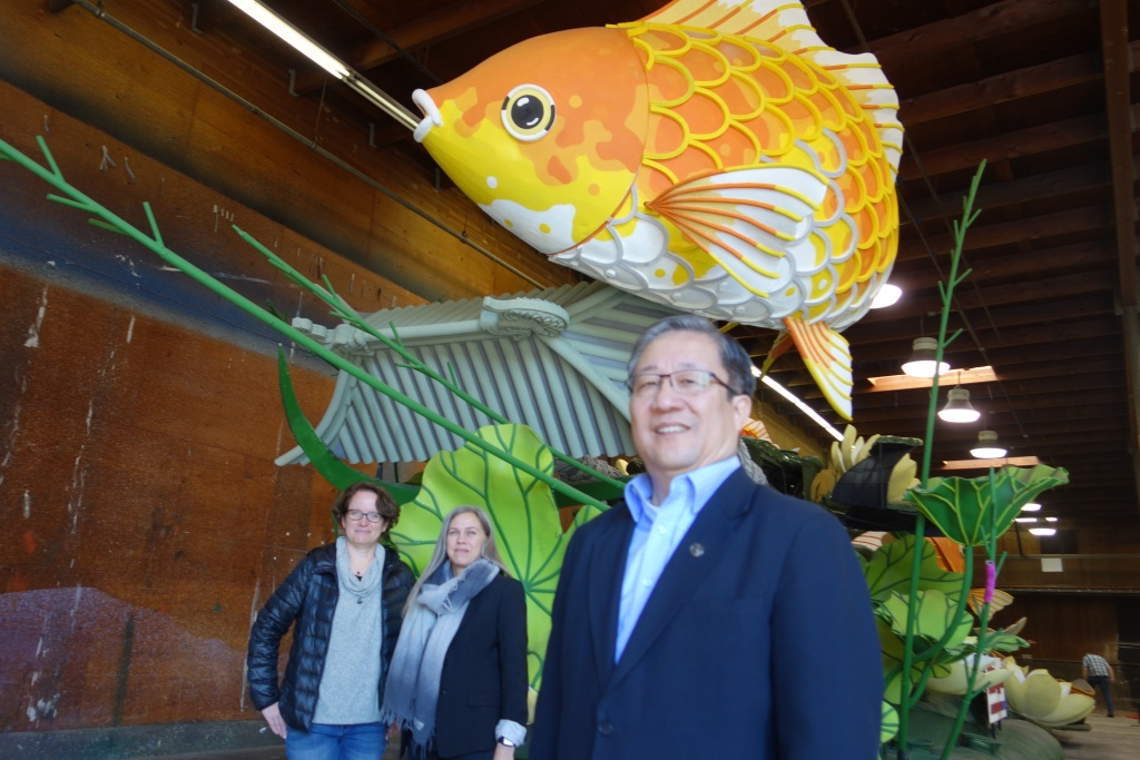 William Chu, CFO of real estate company Singpoli, stands with the company's 2018 Rose Parade float. Behind him are Gwen Robertson of Paradiso Parade Floats, left, and Petra Wennberg Cesario, partner and co-founder of Interactivism, which designed the augmented reality experience for the float.