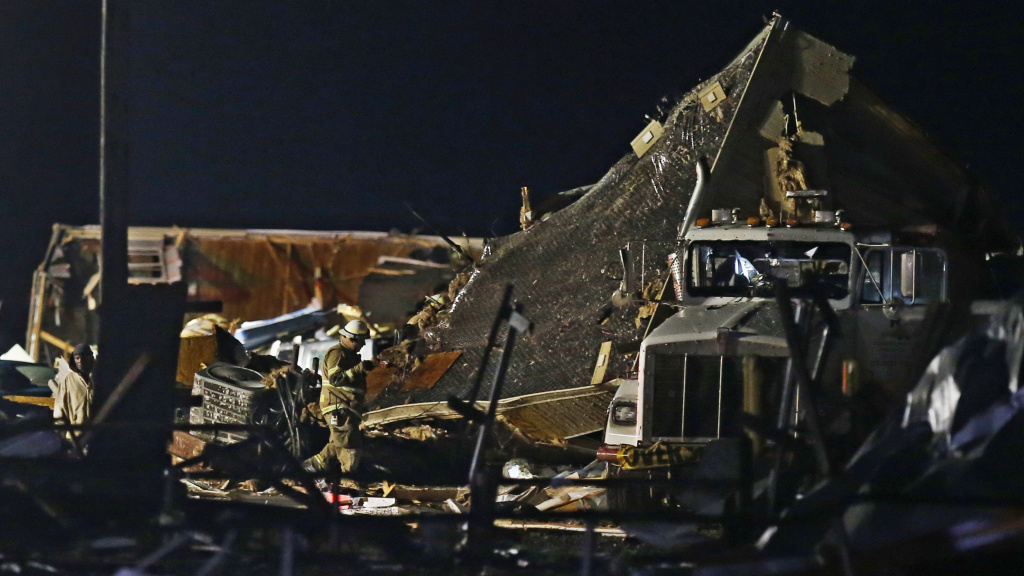 Emergency workers search through debris from a mobile home park in El Reno, Okla. early Sunday.