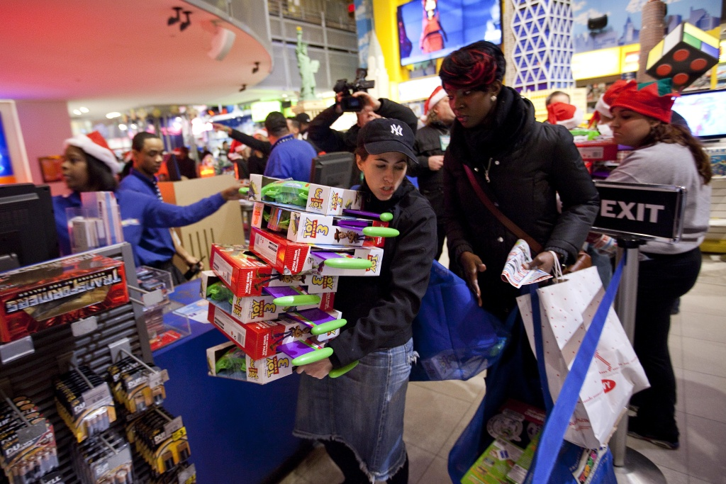 NEW YORK - NOVEMBER 25:  A shopper carries a stack of Toy Story 3 toys at Toys