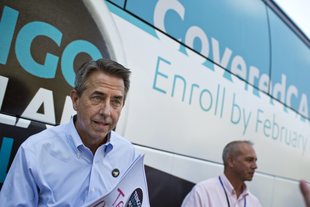 Covered California Executive Director Peter Lee takes photos with attendees during a press conference on Friday, Nov. 15, 2014 at Grand Park kicking off Covered California's second open enrollment period. The event was part of a statewide bus tour that stopped in more than 20 cities to raise awareness about enrollment.