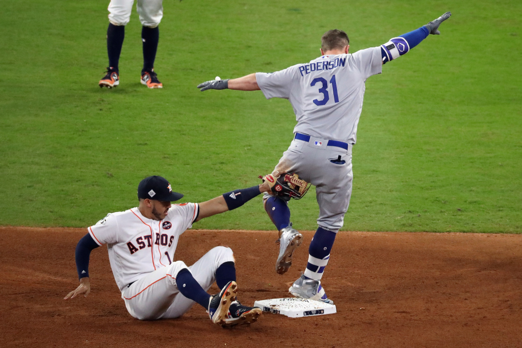 Joc Pederson (#31) of the Los Angeles Dodgers slides in to second after hitting a double as Carlos Correa (#1) of the Houston Astros fails to make the tag during the fifth inning in Game 3 of the 2017 World Series on October 27, 2017 in Houston, Texas.