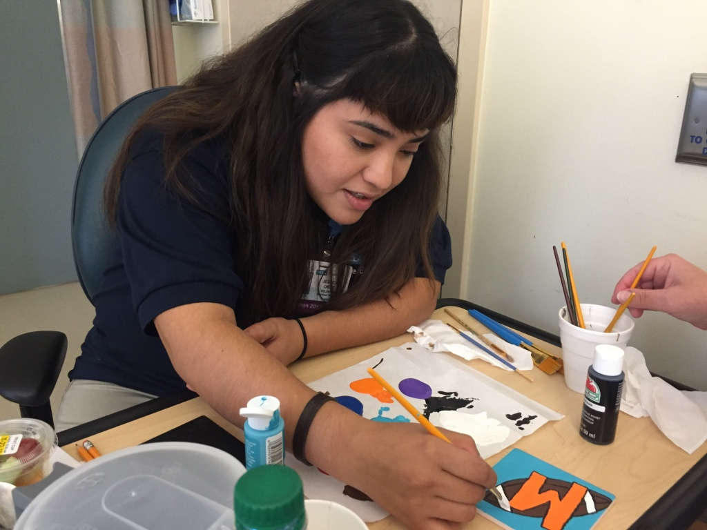 Volunteer Jessica Ortiz helps Rosanna make a coaster.