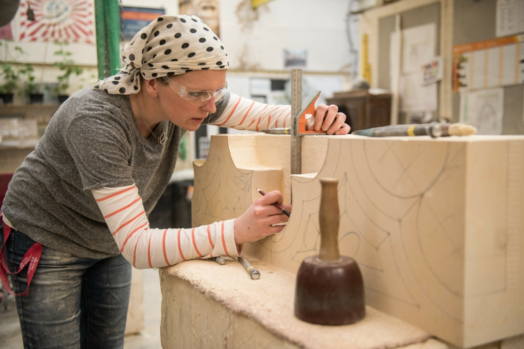 A female stonemason carves new stonework.