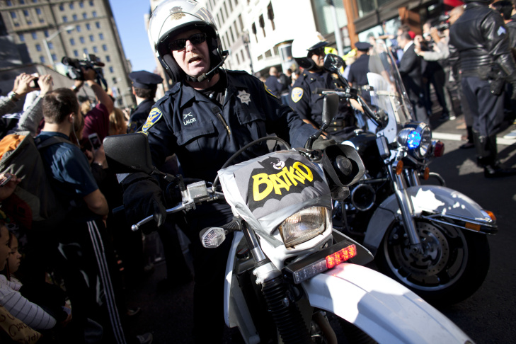 Police escort 5-year-old leukemia survivor Miles, also known as BatKid and Batman after they arrest the Riddler November 15, 2013 in San Francisco. Make-A-Wish Greater Bay Area foundation turned the city into Gotham City for Miles by creating a day long event bringing his wish to be a BatKid to life.