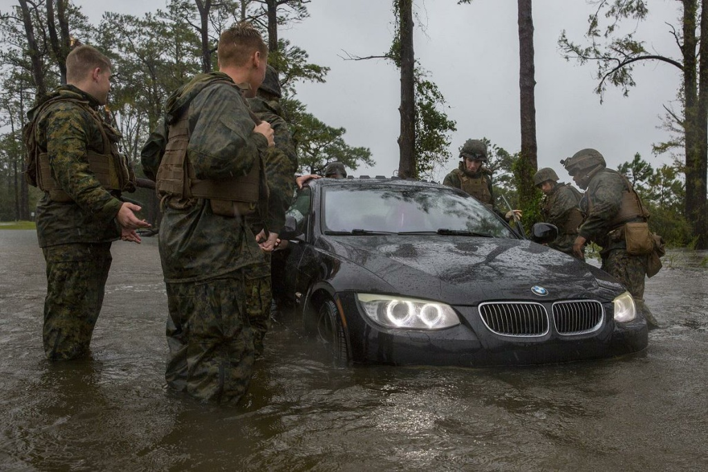 Marines help push a car out of a flooded area at Camp Lejeune, N.C. during Hurricane Florence Sept. 15, 2018. The storm caused billions of dollars in damage to the base.