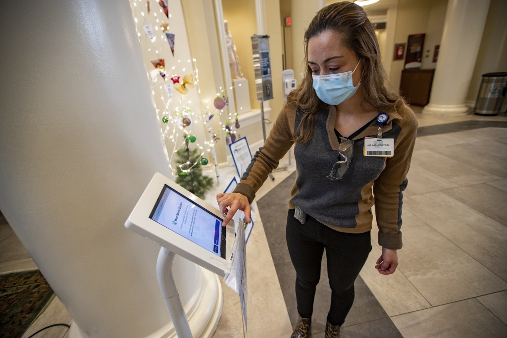Interpreter Ana Maria Rios-Velez demonstrates the screening app at the front entrance of Brigham and Womens Hospital in Boston. It has a multilingual function to better communicate with non-English speaking patients and staff.