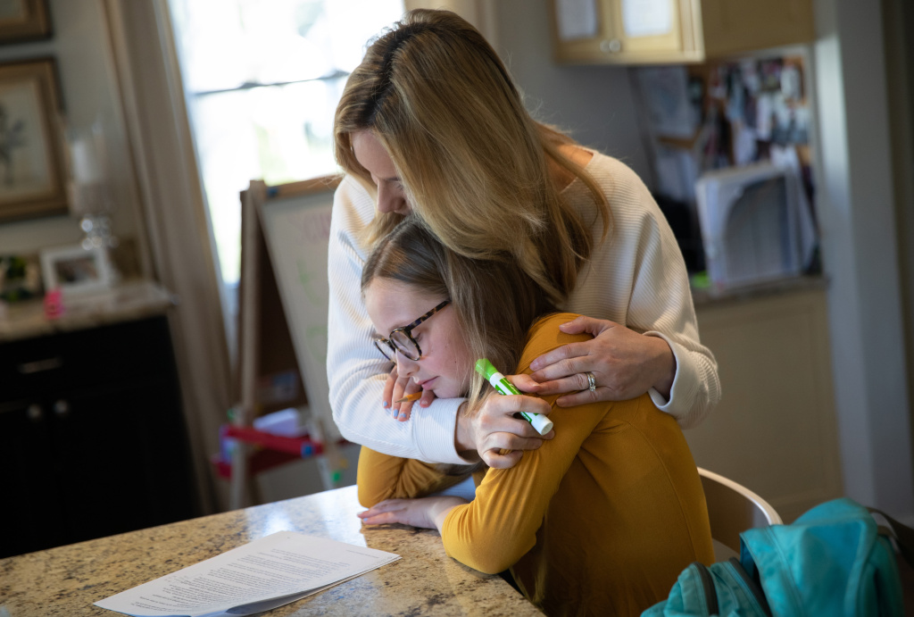Farrah Eaton embraces her daughter Elin, 11, while home schooling on March 18, 2020 in New Rochelle, New York.