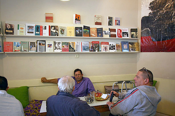 Uri Grosman sits with his friends at Café Yafa. Every Saturday they gather at the cross-cultural cafe to discuss politics and philosophy. Though they seek out the pluralistic atmosphere at Yafa, their hopes for coexistence only go so far.