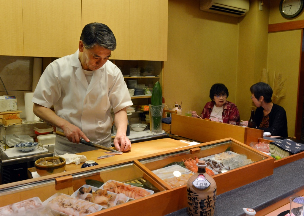 This photo taken on July 16, 2013 shows a chef and restaurant owner preparing sushi for a customer at a high-end sushi restaurant in Tokyo.