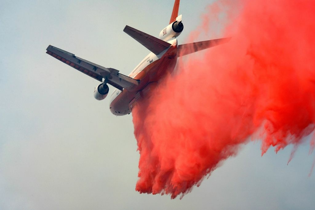 Tanker 910, a DC-10 airliner modified for aerial firefighting, drops fire retardant on the 24-square-mile Butler 2 Fire on September 18, 2007 near Fawnskin, California. The U.S. Fire Service announced that SoCal will now be able to do this type of firefight at night.