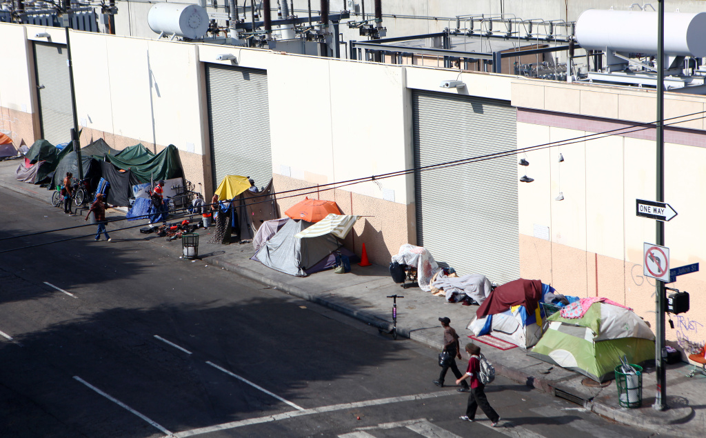 People walk past a homeless tent encampment in Skid Row on September 16, 2019 in Los Angeles, California. Skid Row is home to thousands who either live on the streets or in shelters.