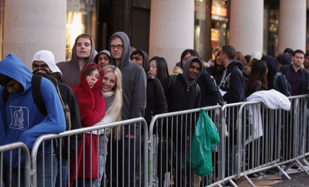 Customers queue outside the Apple store in Covent Garden to buy an iPhone 4S on October 14, 2011 in London, England.