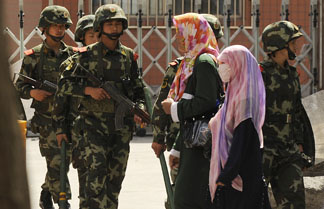 Muslim ethnic Uighur women pass a Chinese paramilatary police on patrol on a street in Urumqi, capital of China's Xinjiang region on July 3, 2010 ahead of the first anniversary of bloody violence that erupted between the region's Muslim ethnic Uighurs and members of China's majority Han ethnicity.