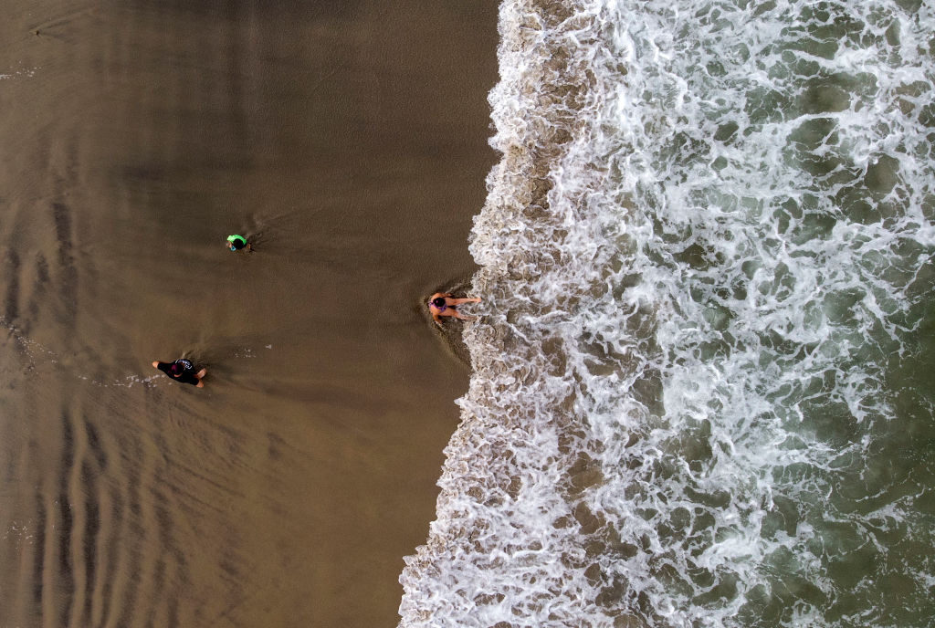 Aerial view showing a girl playing on the shore at the beach in Playas de Rosarito, Baja California State, Mexico, on July 17, 2020, amid the COVID-19 novel coronavirus pandemic, after the municipality allowed a partial use of the beach under a restricted schedule.
