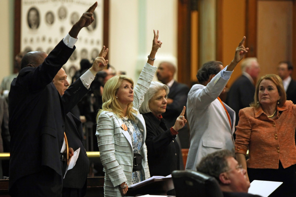 State Sen. Wendy Davis (D-Ft. Worth) (3L) holds up two fingers against the anti-abortion bill SB5, which was up for a vote on the last day of the legislative special session June 25, 2013 in Austin, Texas.