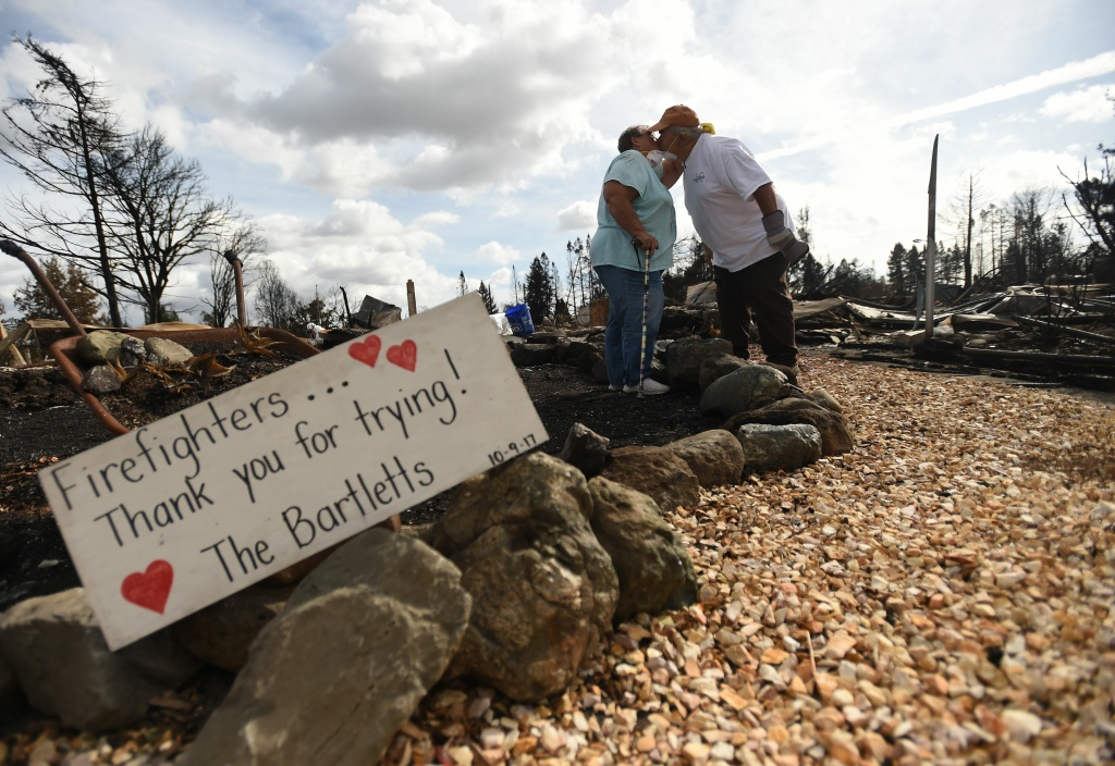TOPSHOT - Byron (R) and Joanne Bartlett (L) pose for a photo in front of a sign they made for firefighters at as they search for remains at their burned residence in the Coffey Park area of Santa Rosa, California on October 20, 2017.  Residents are being allowed to return to their burned homes on October 20 to grieve and search through remains. Around 5,700 homes and businesses have been destroyed by the fires, the deadliest in California's history. / AFP PHOTO / JOSH EDELSON        (Photo credit should read JOSH EDELSON/AFP/Getty Images)