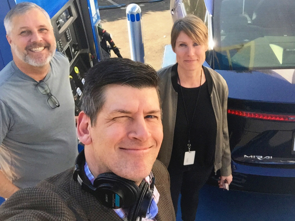 KPCC host John Rabe (foreground) mugs in front of a hydrogen fueling station in South Pasadena with Hydrogen Fuel Cell Partnership spokesman Keith Malone and KPCC motor critic Sue Carpenter.