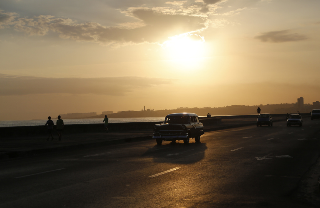 A taxi driver steers his classic American car along the Malecon at sunrise in Havana, Cuba.