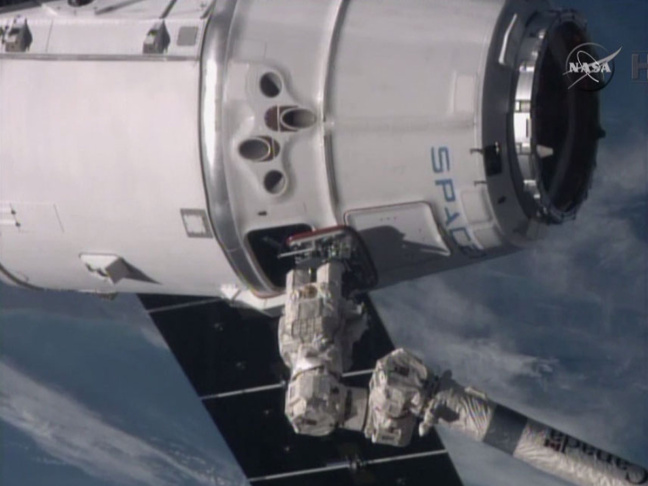 In this video frame grab provided by NASA, the the International Space Station's robotic arm, lower right, operated by station commander Butch Wilmore, reaches for the SpaceX Dragon spacecraft as the soar more than 260 miles above the Mediterranean Sea on Monday, Jan. 12, 2015. The capsule delivered 5,000 pounds of precious cargo, including much-needed groceries and belated Christmas presents, to the space station's six astronauts.