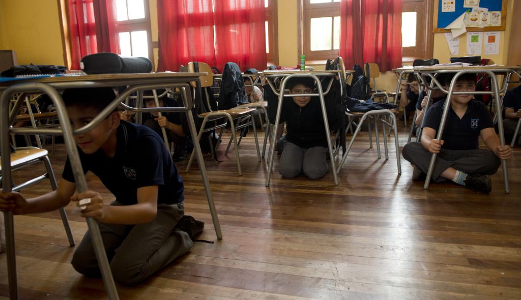 Schoolchildren get cover under the desks during an earthquake drill in Santiago, on November 8, 2012.