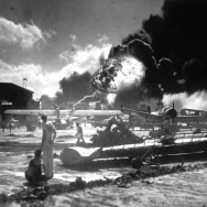Sailors stand among wrecked airplanes at Ford Island Naval Air Station as they watch the explosion of the USS Shaw in the background, during the Japanese surprise attack on Pearl Harbor, Hawaii, on December 7, 1941.