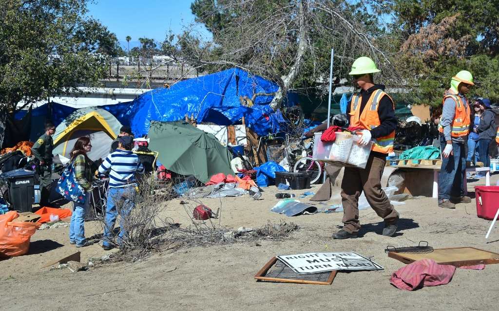 County workers clear and raze a homeless encampment beside the Santa Ana River on February 20, 2018 in Anaheim, California. Officials in Orange County began moving homeless transients out of the homeless tent encampments to shelters or motels as part of the settlement worked out by homeless advocates and the county under supervision of a federal court judge. / AFP PHOTO / Frederic J. BROWN        (Photo credit should read FREDERIC J. BROWN/AFP/Getty Images)