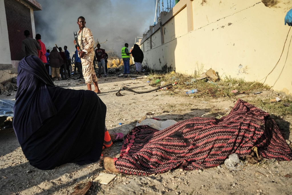 A woman sits by the body of a victim near the site where a truck bomb exploded in the center of Mogadishu on October 15, 2017.
