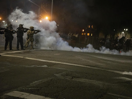 Federal law enforcement officers fire impact munitions and tear gas at protesters demonstrating against racism and police violence in front of the Mark O. Hatfield federal courthouse in Portland, Ore., on July 16, 2020. Through the end of 2020, the majority of last year's federal civil disorder charges were filed in Oregon.
