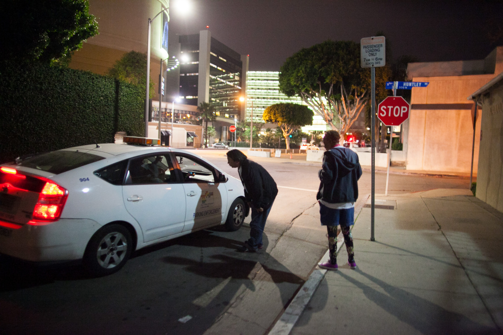 A security patrol stops to offer information on where a group of homeless individuals are sleeping to volunteers Brenda Plantt and Stephan Saengpradap during the homeless census on January 29, 2015.