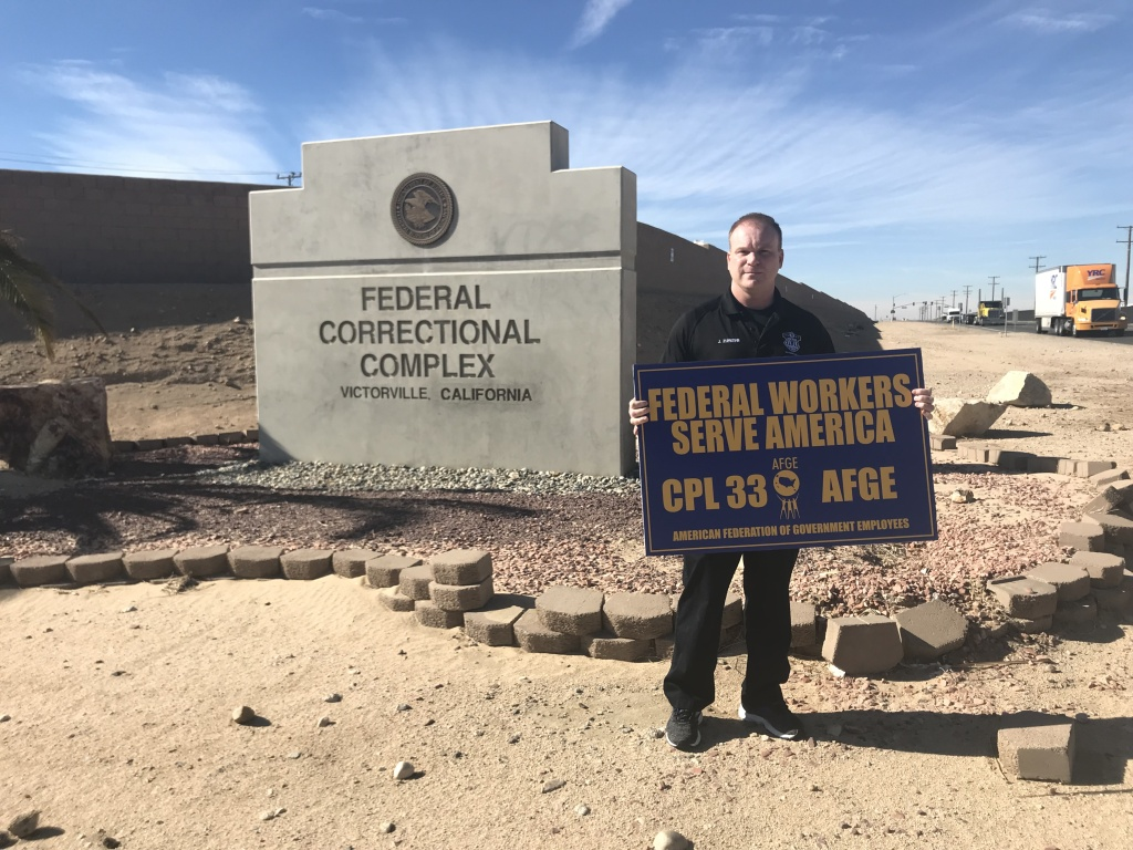 Corrections officer and union leader John Zumkehr stands in front of the entrance to the Victorville Federal Correctional Complex holding a picket sign. Workers here are going without a paycheck during the partial government shutdown.