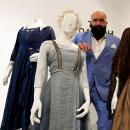 "Costume designer Paco Delgado stands amidst his designs for the film ""The Danish Girl"" on display at the Fashion Institute of Design Museum in Los Angeles."