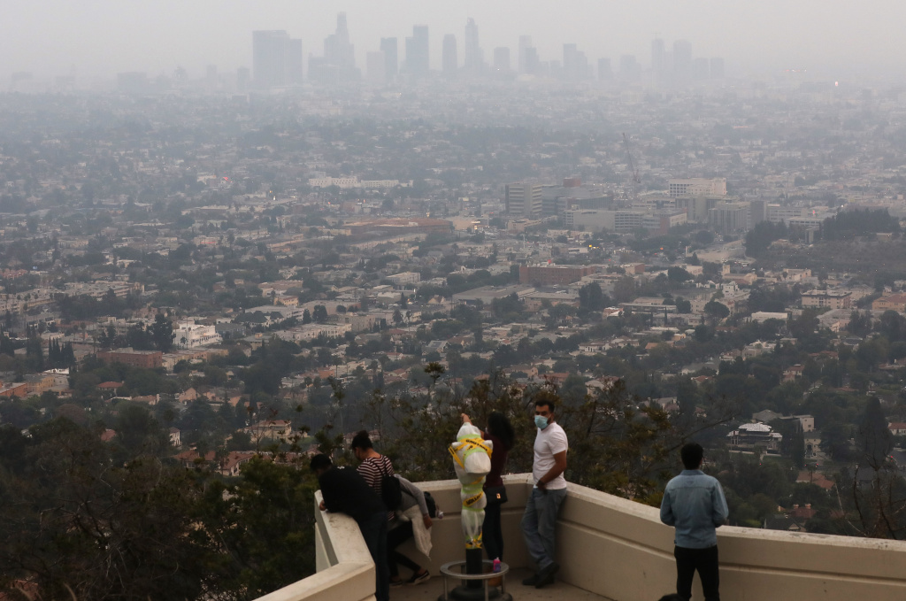 People gather at Griffith Observatory before sunset as the downtown skyline is partially obscured by smoke from wildfires.