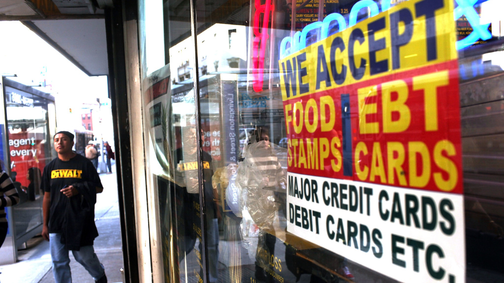 A sign in the window of a New York City market advertises the acceptance of food stamps.