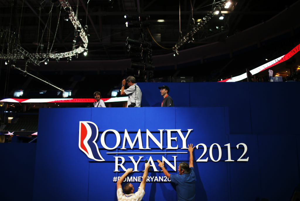Two workers hang a sign ahead of the Republican National Convention at the Tampa Bay Times Forum on August 26, 2012 in Tampa, Florida. The RNC is scheduled to convene on August 27 and will hold its first session on August 28 as Tropical Storm Isaac threatens disruptions due to its proximity to the Florida peninsula.