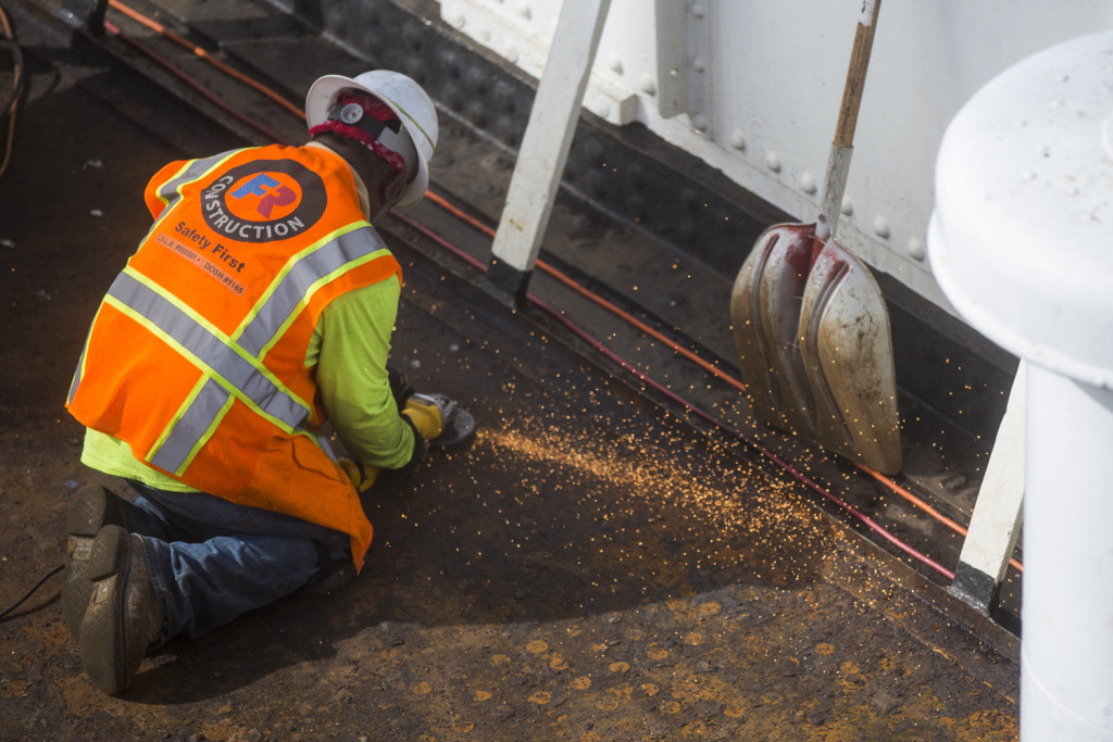 Construction crews work to replacing decking on the well deck on the bow of the Queen Mary in Long Beach on Tuesday, March 14, 2017. The previous deck was not sealed properly and crews are repairing damage underneath.