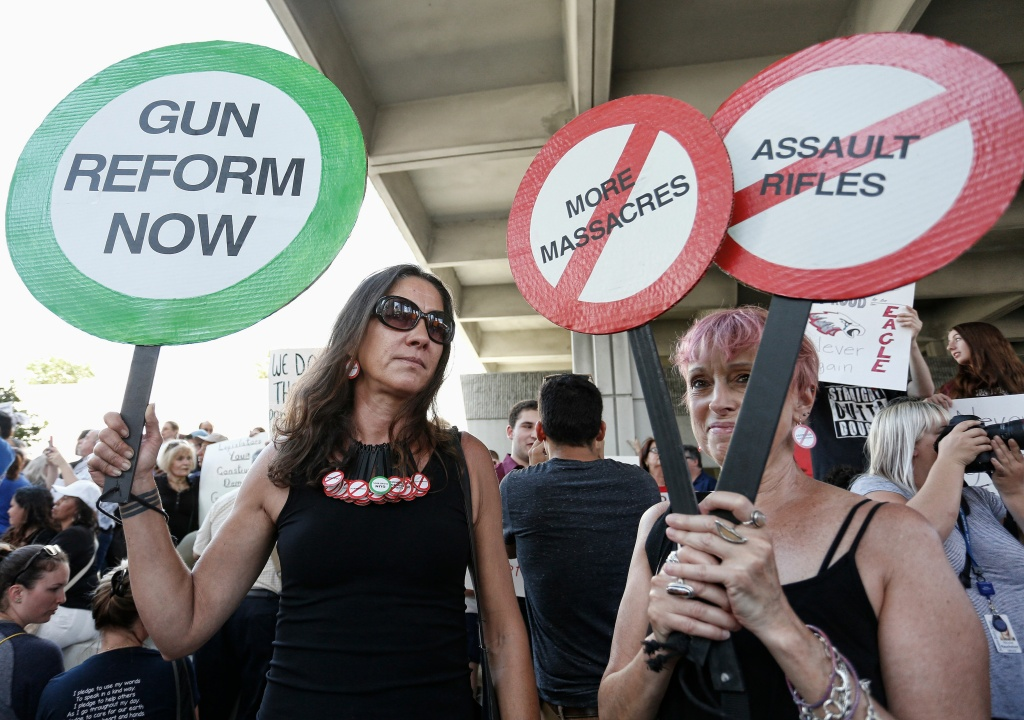 Protesters Alessandra Mondolfi (left) and Mercedes Kent (right) hold signs at a rally for gun control at the Broward County Federal Courthouse in Fort Lauderdale, Florida on February 17, 2018.