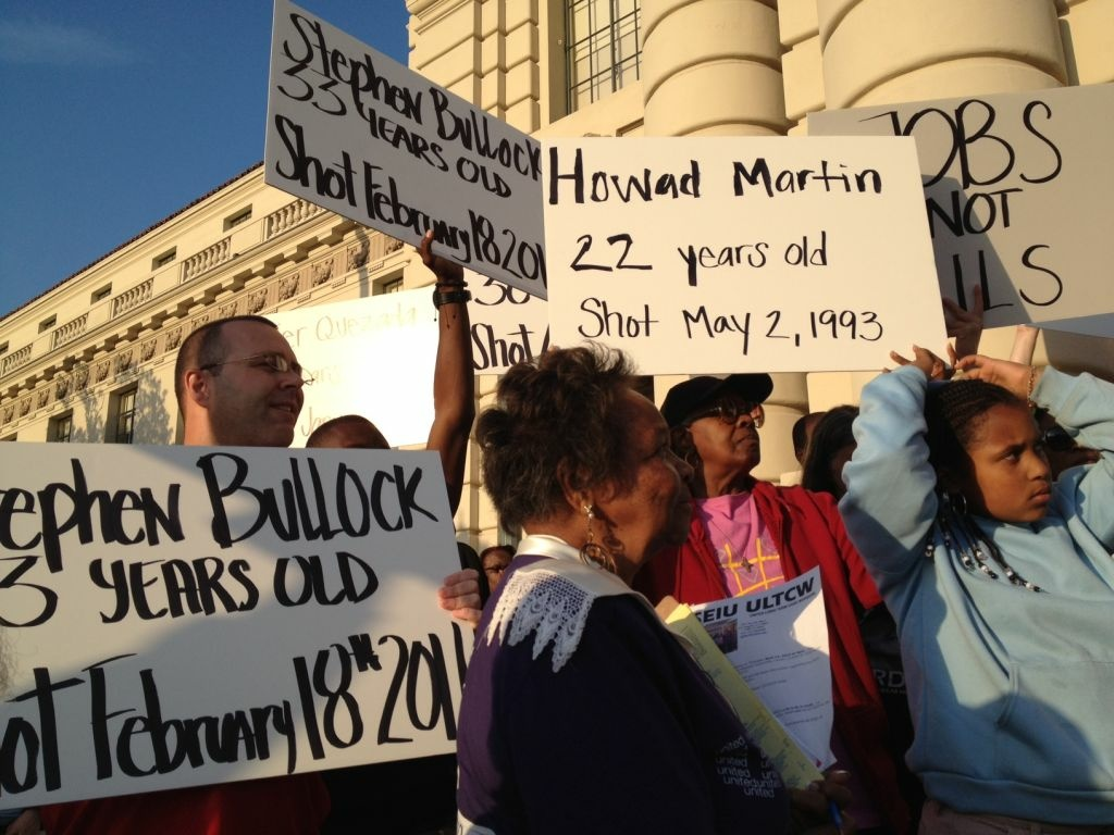 Demonstrators hold signs of other victims of police violence in the L.A. area.
