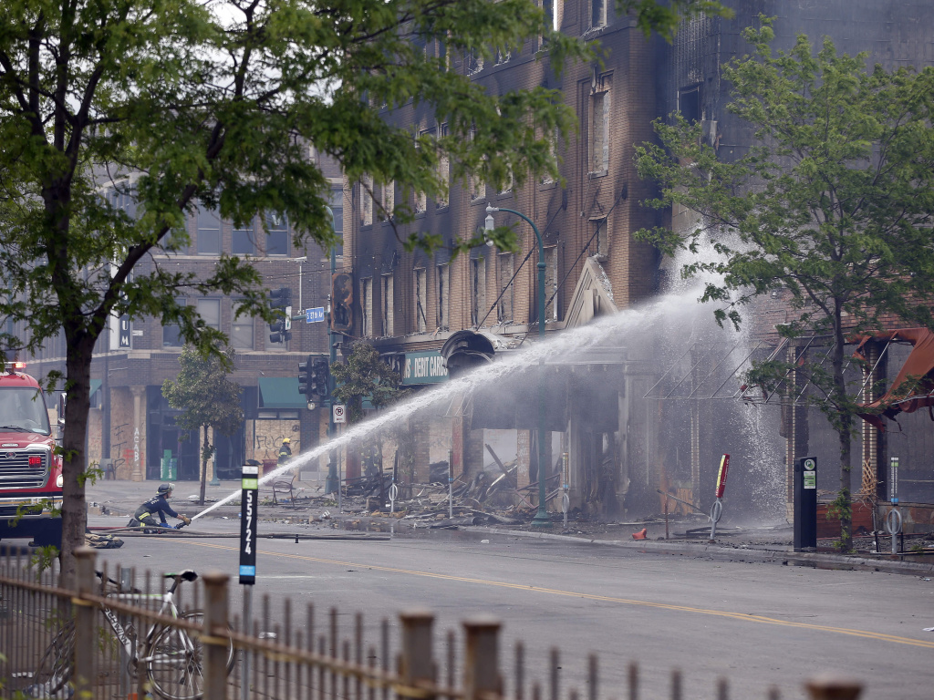 A firefighter directs water on a building that houses El Nuevo Rodeo, a club where George Floyd and Derek Chauvin both worked at one time, former owner Maya Santamaria told KSTP.