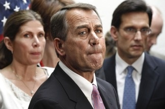 House Speaker John Boehner of Ohio, flanked by House Majority Leader Eric Cantor, R-Va., right, and Rep. Mary Bono Mack, R-Calif., pauses during a news conference on Capitol Hill on April 8, 2011.