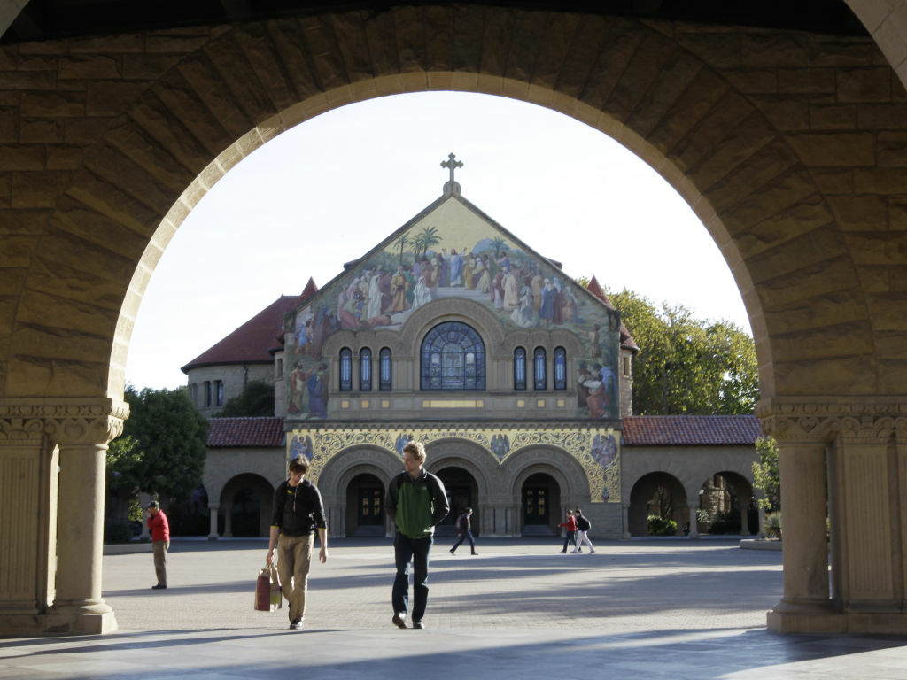 Two students walk in front of Stanford Memorial Church on the Stanford University campus in Stanford, Calif.