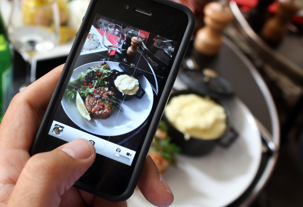 A man takes a picture of his meal with his mobile phone to share it on the