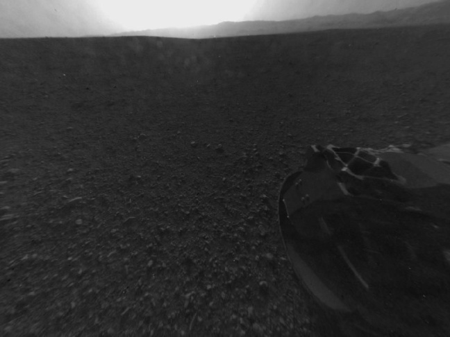 This is the first image taken by the Navigation cameras on NASA's Curiosity rover. It shows the shadow of the rover's now-upright mast in the center, and the arm's shadow at left. The arm itself can be seen in the foreground.