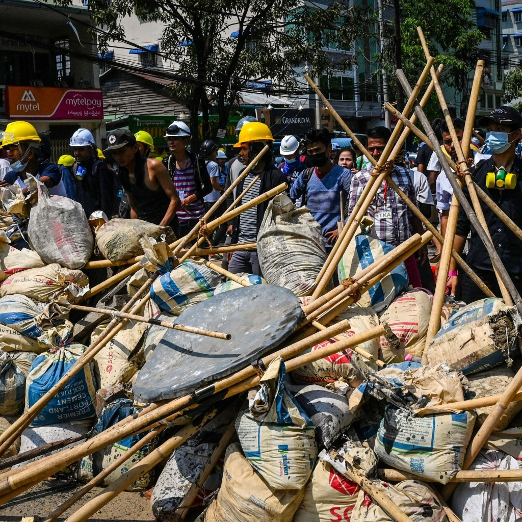 Protesters take cover behind makeshift barricades during a demonstration against the military coup in Yangon's Thaketa township on Friday.