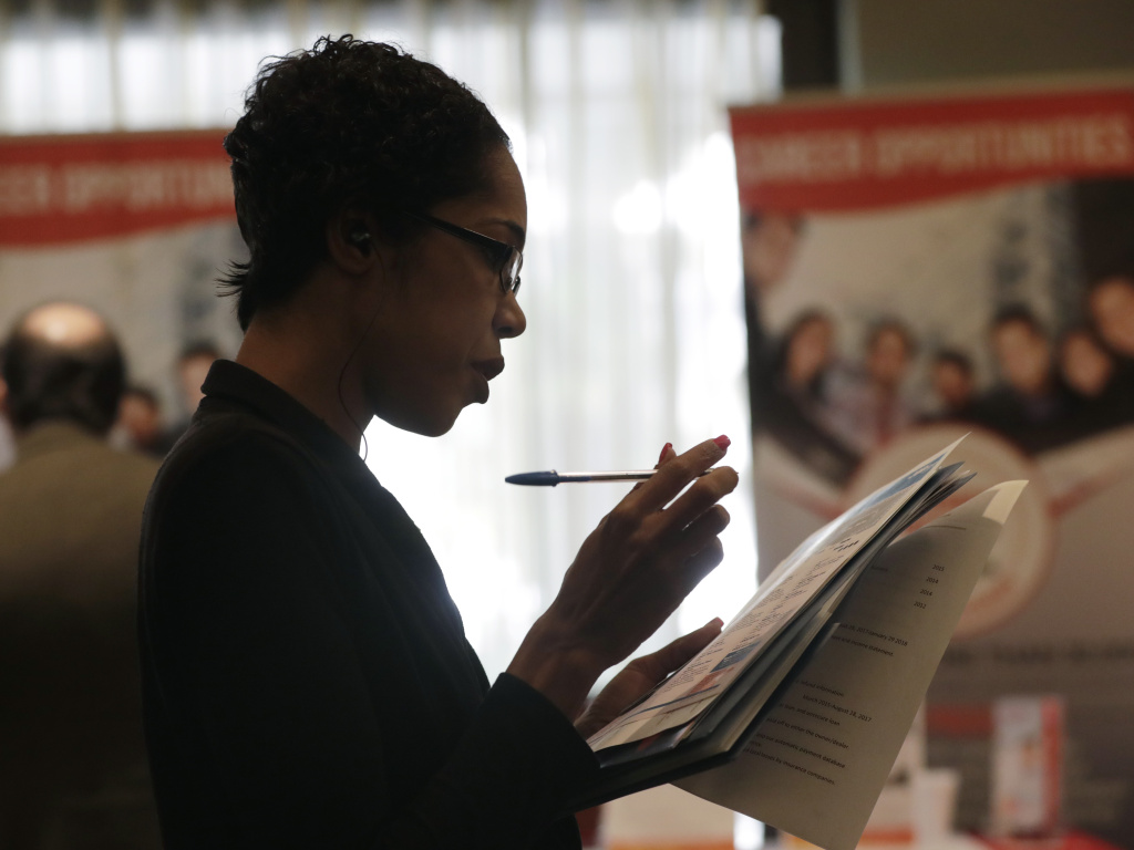 Joana Dudley looks at a list of job prospects at a job fair in Miami Lakes, Fla., in January. Economists say the government's June jobs report is likely to show a continued tightening of the labor market.