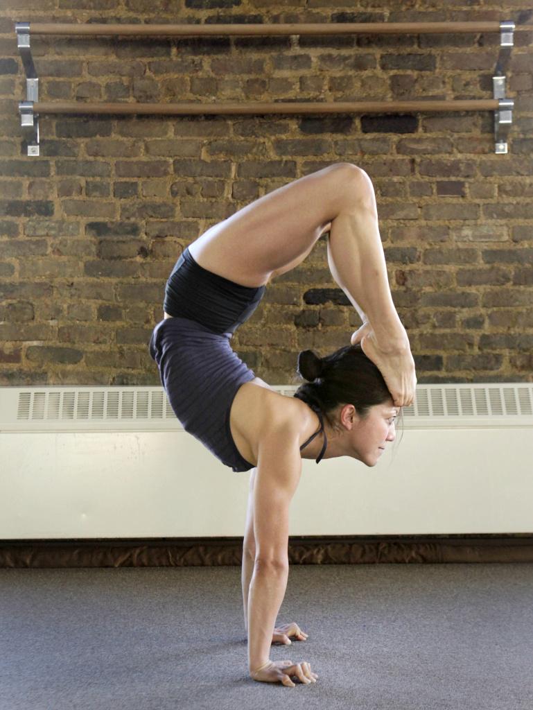 Yoga teacher Kyoko Katsura demonstrates handstand scorpion.