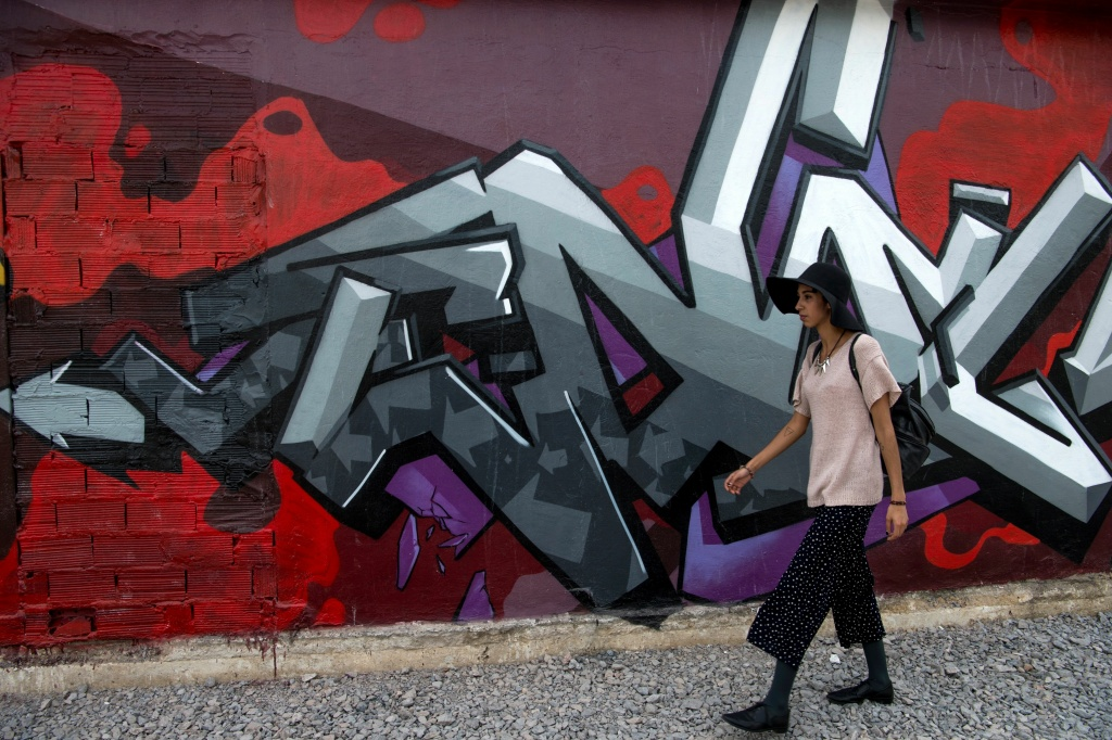 A woman walks past an street art in Rabat, Morocco.