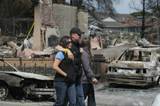 A couple walks by homes that were destroyed by fire following a deadly gas main explosion on September 13, 2010 in San Bruno, California.