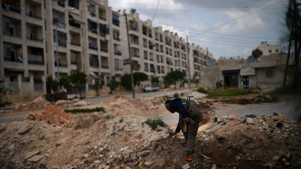 A Syrian rebel patrols the area in the Sheikh Maqsud district of the northern Syrian city of Aleppo, on Thursday.