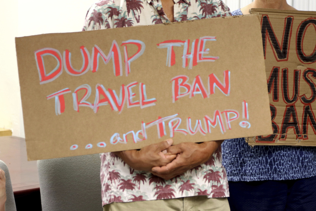 FILE- In this June 30, 2017, file photo, critics of President Donald Trump's travel ban hold signs during a news conference with Hawaii Attorney General Douglas Chin in Honolulu. A federal judge in Hawaii on Thursday, July 6, left Trump administration rules in place for a travel ban on citizens from six majority-Muslim countries. U.S. District Court Judge Derrick Watson denied an emergency motion filed by Hawaii asking him to clarify what the U.S. Supreme Court meant by a