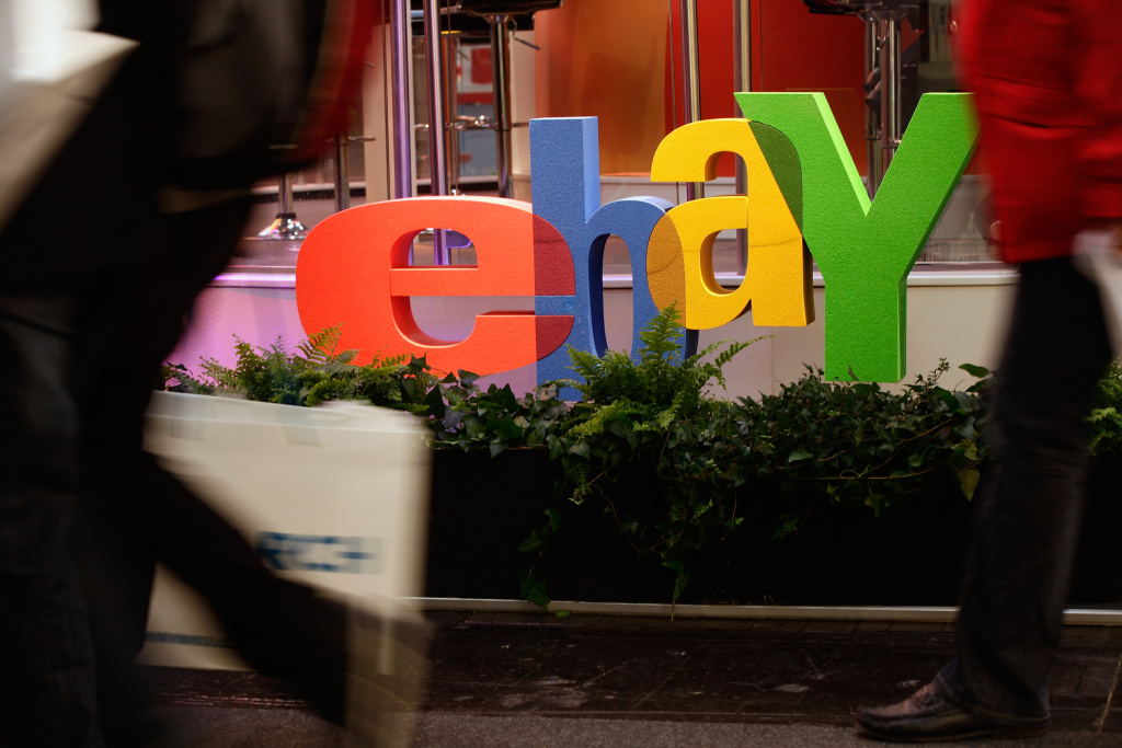 Visitors walk past the logo of online retailer eBay at the CeBIT technology trade fair on March 1, 2011 in Hanover, Germany.